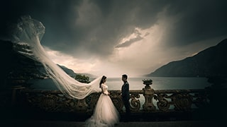 cristiano-ostinelli-sony-alpha-7RIII-bride-and-groom-on-balcony-with-dress-billowing-in-wind