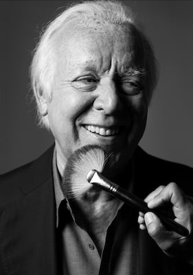 kenton-thatcher-sony-alpha-9-black-and-white-portrait-of-a-man-smiling-as-he-has-make-up-applied